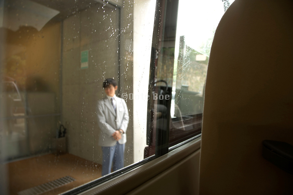 hotel attendant waiting for guests coming from a minibus