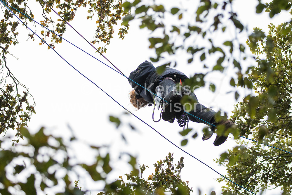 An anti-HS2 activist crosses between trees about sixty feet above ground at a wildlife protection camp in ancient woodland at Jones' Hill Wood on 6 October 2020 in Aylesbury Vale, United Kingdom. The Jones' Hill Wood camp, one of several protest camps set up by anti-HS2 activists along the route of the £106bn HS2 high-speed rail link in order to resist the controversial infrastructure project, is currently being evicted by National Eviction Team bailiffs working on behalf of HS2 Ltd.