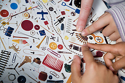 Children pointing to picture of crown on sheet of objects,