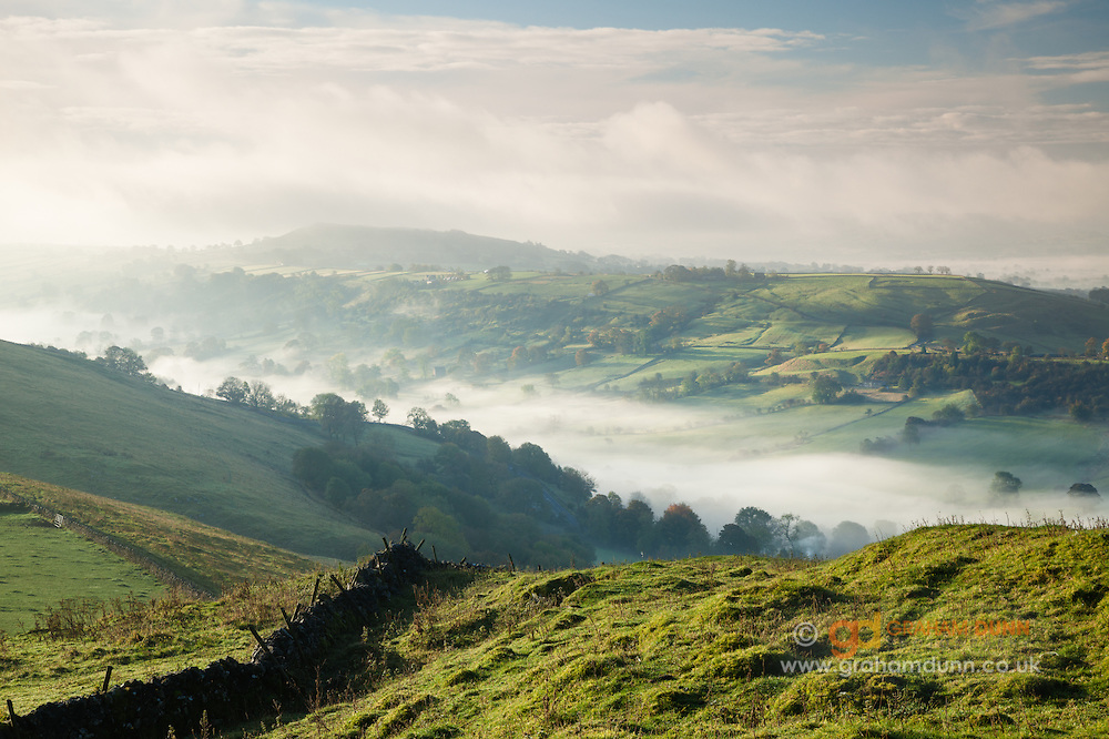 Sheen Hill, partially engulfed in cloud, stands over a mist-filled Upper Dove Valley. Peak District.