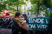 """01/05/2015 – Berlin, Germany: A couple kisses on the street while member of the radical left pass by during the """"Revolutionary 1st of May Demonstrations"""" in Kreuzberg to celebrate the Workers Day. The International Workers Day is a celebration of laborers and the working classes that is promoted by the international labor movement, anarchists, socialists, and communists and occurs every year on May Day. (Eduardo Leal)"""