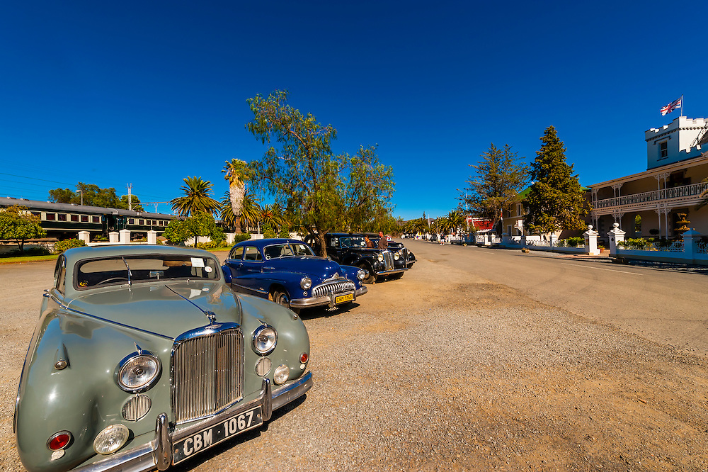 """Vintage cars on display,  Matjiesfontein. Rovos Rail train """"Pride of Africa"""" on it's journey between Pretoria and Cape Town, South Africa."""