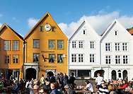 People sitting at outdoor tables drinking beer on a warm summer evening in Bryggen, Bergen, Norway, Europe