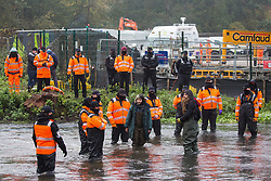 HS2 security guards monitor anti-HS2 activists standing in the river Colne at Denham Ford in order to try to delay bridge building works for the HS2 high-speed rail link on the first day of the second national coronavirus lockdown on 5 November 2020 in Denham, United Kingdom. Prime Minister Boris Johnson has advised that construction work may continue during the second lockdown but those working on construction projects are required to adhere to Site Operating Procedures including social distancing guidelines to help prevent the spread of COVID-19.
