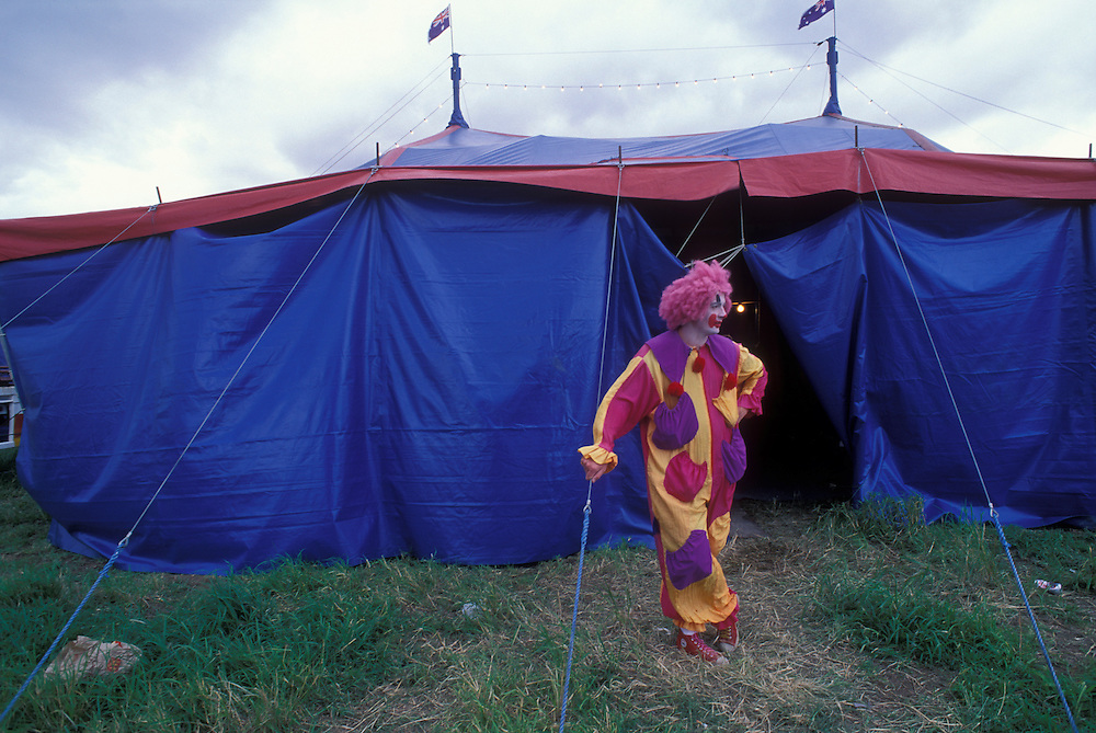 Australia, New South Wales, (MR)  'Mr. Jellybeans' Paul Lockley waits for show's start outside Montana Ice Circus tent in Minchinburg