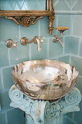 Sterling silver bath wash basin with light blue tile bathroom