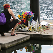 A mourner is seen at a small makeshift memorial at Lake Eola Park flagpole for the victims of the Pulse nightclub where many victims were killed in the deadliest shooting in modern U.S. History on Tuesday,   June 14, 2016, in Orlando, Fla. (Alex Menendez via AP)