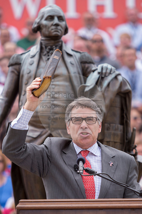 """Former Texas Gov. Rick Perry holds a bible as he address a gathering of evangelical Christians during the """"Stand With God"""" rally  August 29, 2015 in Columbia, SC. Thousands of conservative Christians gathered at the State House to rally against gay marriage and listen to GOP presidential candidates Gov. Rick Perry and Sen. Ted Cruz speak."""