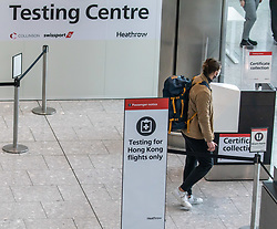 © Licensed to London News Pictures. 20/10/2020. London, UK. A passenger walks past a testing centre at Heathrow Terminal 5. A one hour Covid-19 testing centre at London Heathrow for Hong Kong and Italy passengers has opened up at London Heathrow. Two facilities one at Terminal 5 and the other at Terminal 2 will offer much quicker results than the NHS as samples don't need to be sent away to be tested. Prime Minister Boris Johnson is expected to announce a Tier 3 lockdown for Manchester tonight as coronavirus levels of infections continue to escalate throughout the UK. Photo credit: Alex Lentati/LNP