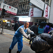 Street cleaner at work in Central. The streets of Hong Kong are kept clean by an army of street cleaners, many elderly men and women. 7 million people live on 1,104km square, making it Hong Kong the most vertical city in the world.