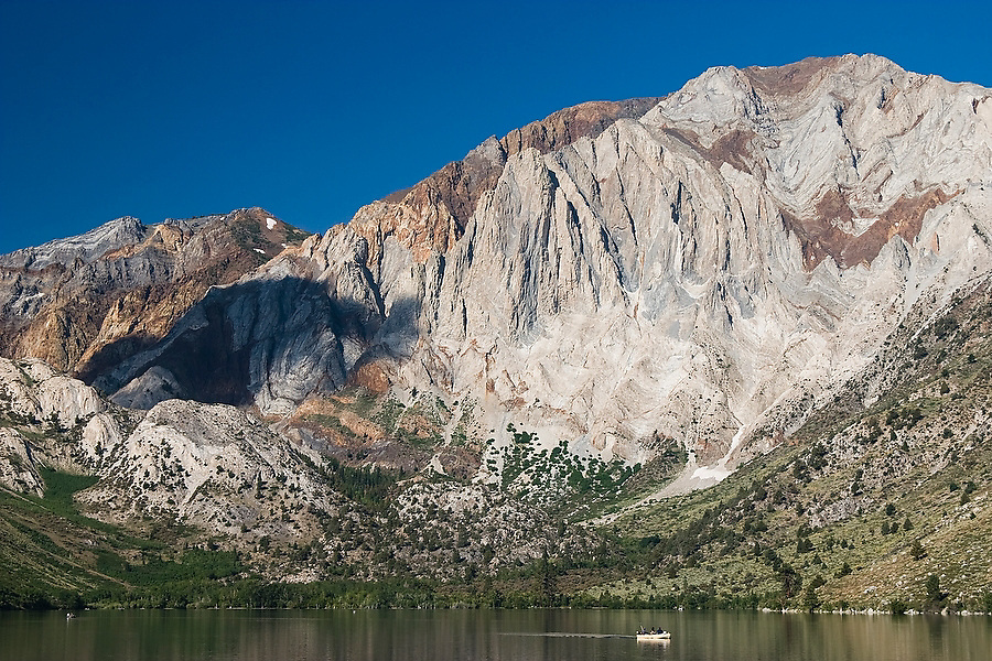 A boat crosses Convict Lake below dramatic cliffs near Mammoth Lakes in the Eastern Sierras, California.