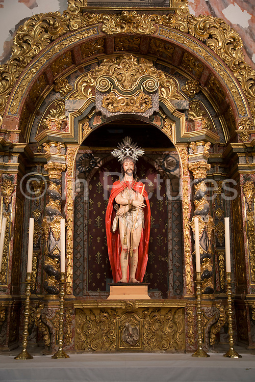 The Alhambra Palace and fortress complex located in Granada, Andalucia, Spain. Figure of Christ inside the Church of Santa Maria de la Alhambra.