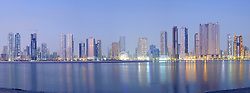 Night skyline panoramic view of modern high-rise apartment buildings along Corniche in Sharjah United Arab Emirates