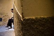A man counts his coins in a narrow alleyway in the medieval city of Fes El-Bali, Morocco.
