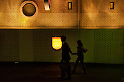 A couple walk passed the wall and Illuminated sign for a love hotel or fashion hotels as they are called in Dogenzaka ((Love Hotel Hill)), Shibuya, Tokyo, Japan. Friday April 18th 2014