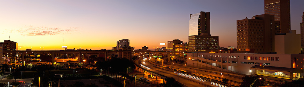 Panoramic twilight view of downtown Miami office and residential high rise buildings, Metrorail elevated train tracks and adjacent expressway ramps to and from US Route 95. WATERMARKS WILL NOT APPEAR ON PRINTS OR LICENSED IMAGES.