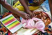 Medical attendant Sophia goes through the new baby checklists with a mother on the  NICU (Neonatal Intensive Care Unit) ward. St Walburg's Hospital, Nyangao. Lindi Region, Tanzania.