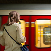 Woman waiting for a London Underground train on a platform