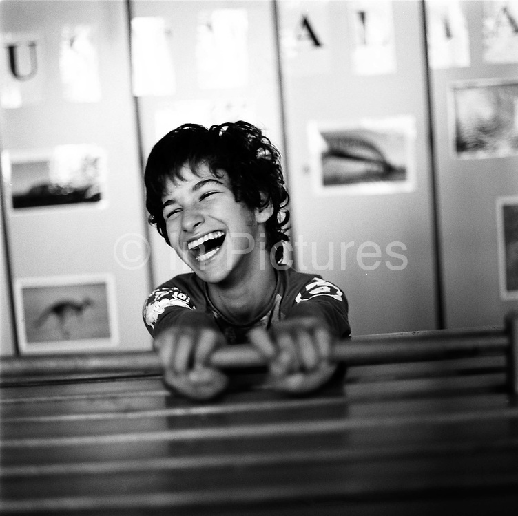 A girl with learning difficulties and cerebal palsy laughs during a lesson at the Peto Instiute. She is seen gripping handles at ther desk that keep her body in position in accordance with the Peto's methods.<br /> Designed by Dr Andras Peto in the 1940's in Budapest, Conductive education is a unique system of teaching and learning for children with motor disorders such as cerebral palsy and spina bifida. Designed to improve motor skills and increase independence, it is a method of intense exercise and education.