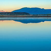 The Glass Mountains of the Eastern Sierra Nevada (and a photographer) reflect in Big Alkali Lake in Long Valley near Mammoth Lakes, California.