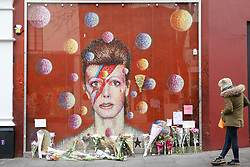 © Licensed to London News Pictures. 10/01/2019. London, UK. A fan reads the tributes that are placed on a mural and shrine to David Bowie in Brixton, on the third anniversary of his death. Photo credit: Dinendra Haria/LNP