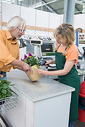 Customer buying potted plant from a garden centre, Augsburg, Bavaria, Germany