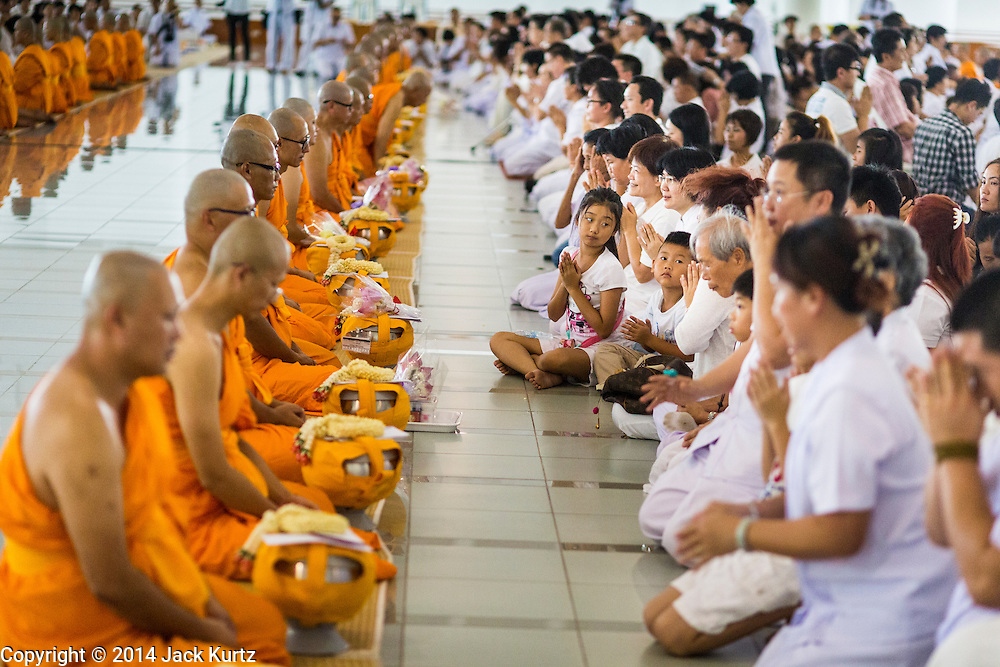19 JULY 2014 - KHLONG LUANG, PATHUM THANI, THAILAND: Newly ordained monks and novices and members of their families pray together before lunch in the canteen at Wat Phra Dhammakaya. Seventy-seven men from 18 countries were ordained as Buddhist monks and novices at Wat Phra Dhammakaya, a Buddhist temple  north of Bangkok, Saturday. It is the center of the Dhammakaya Movement, a Buddhist sect founded in the 1970s and led by Phra Dhammachayo (Phrathepyanmahamuni). It is the largest temple in Thailand. The Dhammakaya sect has an active outreach program that attracts visitors from around the world.    PHOTO BY JACK KURTZ