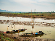 02 APRIL 2016 - NA SAK, LAMPANG, THAILAND: Fishermen's canoes tied up near the original site of Sobjant village. The village of Sobjant in Na Sak district in Lampang province was submerged when the Mae Chang Reservoir was created in the 1980s. The village was relocated to higher ground a few kilometers from its original site. The drought gripping Thailand drained the reservoir and the foundations of the Buddhist temple in the original village became visible early in 2016. Thai families come down to the original village to pray in the ruins of the temple and look at what's left of the village.      PHOTO BY JACK KURTZ