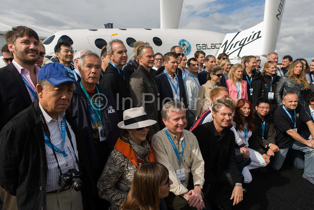 Some of the 529 (correct at July 2012) signed up Virgin Galactic astronauts gather by SpaceShipTwo model for another announcement by company executives at a PR event during the Farnborough Air Show. Virgin Galactic is one of the leading potential space tourism groups, is planning to begin passenger service aboard the VSS Enterprise, a Scaled Composites SpaceShipTwo type spacecraft. The initial seat price is $200,000, with a required down payment of $20,000. Headed by Sir Richard Branson's Virgin Group, Virgin Galactic hopes to be the first private space tourism company to regularly send civilians into space. A citizen astronaut will only require three days of training before spaceflight.