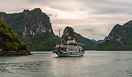 Ha Long Bay, Vietnam -- March 24, 2016 Tour boat  navigates through the rock dramtic formations in Ha Long Bay, Vietnam. Editorial Use Only.