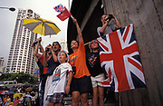 A British family hoping to catch a glimpse of passing VIPs, wave Union Jack flags on the eve of the handover of sovereignty from Britain to China, on 30th June 1997, in Hong Kong, China. That night signified the end of British rule, and the transfer of legal and financial authority back to China. Hong Kong was once known as fragrant harbour or Heung Keung because of the smell of transported sandal wood.