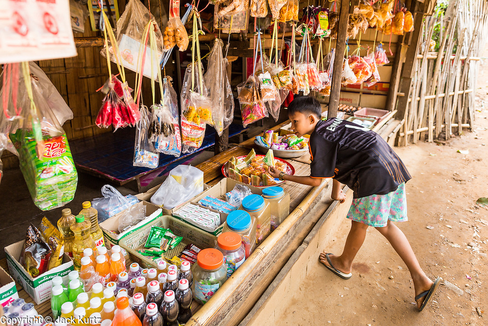 22 MAY 2013 - MAELA REFUGEE CAMP, TAK, THAILAND:     A Burmese boy shops for snacks in a small snack stand in Mae La (Maela) is the largest refugee camp for Burmese in Thailand. Over 90% are ethnic Karen. It was established in 1984 in Tha Song Yang District, Tak Province in the Dawna Range area and currently houses 40,000 refugees. The Thai government has indicated that it would like to close the camp and repatriate the refugees to Myanmar as soon as the political situation in Myanmar is stable enough.   PHOTO BY JACK KURTZ