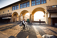 A man cycling on Ponte Vecchio at sunrise