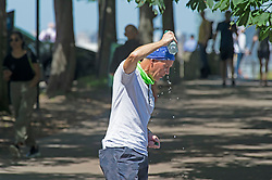 © Licensed to London News Pictures 16/07/2021. Greenwich, UK. A man pouring water over his head to cool down in Greenwich Park, London as a hot weather warning is issued for this weekend with temperatures expected to hit 30C. Photo credit:Grant Falvey/LNP