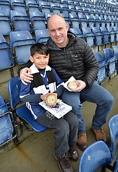 Pictured: 9 year old Joshua Holt with his dad Kenny looking forward to the match at Falkirk.<br /> <br /> How many Scottish football fans promise themselves a trip to every senior football ground in the country sometime in their life? Probably the majority when they retire.  One such fan who decided to get that milestone ticked off early in his life is nine year old Joshua Holt, from Edinburgh and an Edinburgh City fan, who completed his tour on Saturday 30 December at the Falkirk Stadium when Queen of the South are the visitors.  It has taken four years for Joshua, accompanied by his father Kenny, to complete the tour which started off on 31 August 2013 at Ibrox when Rangers took on East Fife.  A goal feast was on offer that day as Rangers won 5-0 but Joshua, like most five year olds, was more interested in everything else that accompanies a trip to one of the biggest stadiums in the UK.  His father, however, noticed a lot more than the football on the pitch; he had discovered what his football had been missing – a like minded companion.  This was their 'thing' to do together; father and son; come rain or shine.  Not the 'quality time' so often quoted as an essential for a parent but real time doing something they both enjoy.  A shared experience can build stronger bonds than any amount of treats from father to son.  They have travelled over five and a half thousand miles on their long journey and have enjoyed an average 2.9 goals per game.  Not a bad return for the commitment they have shown.<br /> <br /> Fans on match days have their own rituals, be it their lucky scarf; same bus for away games; or heading to the same seat for home games.  Joshua and Kenny go for the four Ps; popcorn, pin badge, programme and pie.  Popcorn for the trip to the ground with the programme and pin badges bought from the club shop as a reminder of the visit.  The catering is always tested especially on these cold days.  For the record Joshua can't see past a Dunfermline pie but his dad