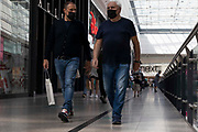 Two men wearing face masks, one carrying a bag of shopping, converse as they walk through Manchester city centres Arndale shopping centre on 26th August, 2021 in Manchester. Many of the UKs high streets and shopping centres are bustling once again, welcoming shoppers back as footfall slowly climbs back to levels seen before the restrictions brought about by the Covid-19 pandemic.