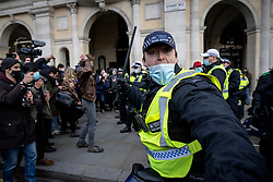 © Licensed to London News Pictures. 03/04/2021. London, UK. A police officer raises his baton as they attempt to disperse Kill the Bill protesters in Trafalgar Square. Protests have been held across the UK in opposition to the Police, Crime, Sentencing and Courts Bill which would broaden police powers when dealing with protests. Photo credit: Rob Pinney/LNP