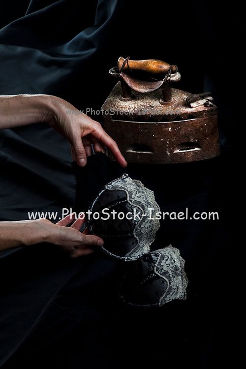 Dark and moody photograph of a woman holding an old style bra. An old fashioned coal iron in the background