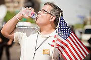 "29 JULY 2010 - PHOENIX, AZ: A protester drinks a bottle of water while waiting to be arrested Thursday morning. Dozens of people were arrested during protests against SB 1070 across central Phoenix Thursday. US Judge Susan Bolton's ruling Wednesday stopped four of SB 1070's more than a dozen provisions from going into effect. She wrote, ""The court also finds that the United States is likely to suffer irreparable harm if the court does not preliminarily enjoin enforcement of these sections,"" she states in the ruling. ""The balance of equities tips in the United States' favor considering the public interest.""    PHOTO BY JACK KURTZ"