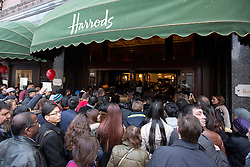 © Licensed to London News Pictures. 26/12/2013. London, UK. Shoppers squeeze through an entrance of the world famous Harrods department store as it begins it's Boxing Day sale in London today (26/12/2013). Photo credit: Matt Cetti-Roberts/LNP