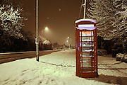 A red phone box in the snow.
