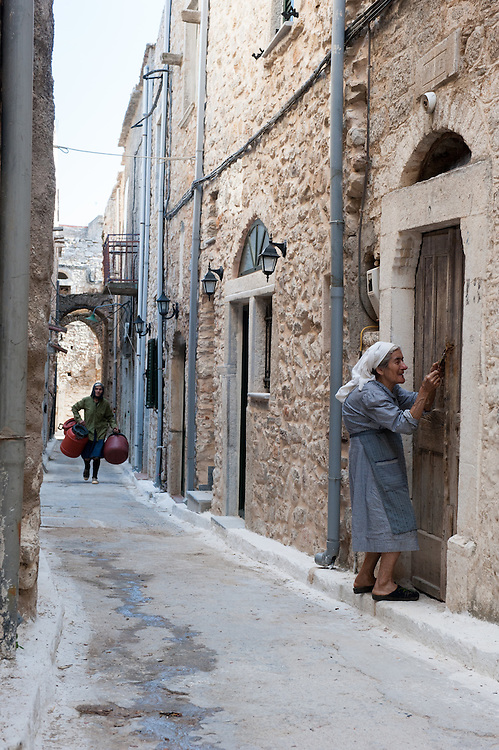 """An elderly woman entering her old house in an alley in the medieval village of Pyrgi, Chios, Greece. <br /> <br /> Pyrgi in Chios is known as the """"painted village"""" on account of the decoration of the houses. The village still keeps its medieval style and together with the other Mastichochoria (Mastic Villages) are in the list of the Intangible Cultural Heritage of Humanity of UNESCO"""