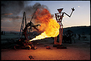 "Christian Ristow's bulldozer-tracked, raptor-clawed robot, called Subjugator, fires its flame thrower during a test run for his apocalyptic show of mechanical mayhem at the Burning Man Festival in Nevada's Black Rock Desert. A former Columbia University architecture student who is now an artist in Los Angeles, Ristow stages mechanical performances in which his constructions fight each other and destroy designated sacrificial targets. With typical bravado, he called his Burning Man show, ""The Final Battle of the Twentieth Century Between Man and Machine for Ultimate Supremacy on the Earth."" From the book Robo sapiens: Evolution of a New Species, page 198-199."