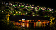 Bridge over the Danube in Bratislava by night. Green lights, Reflections in the water. Lighted Castle in the background