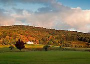Fall foliage dresses the rolling hills of Vermont in rich warm colors as the afternoon sun plays across grassy fields.