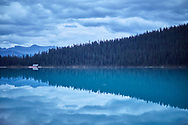 A mirror reflection looking across Lake Louise towards a boathouse as a storm approaches from beyond.