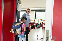 Female teacher welcoming student in classroom on first day of school, Munich, Bavaria, Germany
