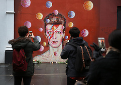 © Licensed to London News Pictures. 11/01/2016. London, UK. People take phone photos at a mural of David Bowie in Brixton. The Death of David Bowie, who was born in Brixton, has been announced today.  Photo credit: Peter Macdiarmid/LNP
