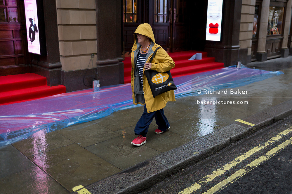 A passer-by walks alongside the rain-soaked red carpet awaiting crowds who will be seeing the English National Opera's opening night of Orpheus and Eurydice at the Coliseum on St. Martin's Lane, on 1st October 2019, in London, England.