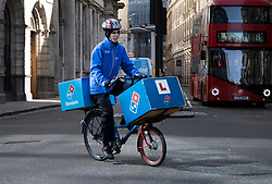 © Licensed to London News Pictures. 24/03/2020. London, UK. A Domino's Pizza delivery cyclist makes his way along Threadneedle Street in the City of London after Prime Minister Boris Johnson announced that the UK will now lockdown in order to fight the spread of the coronavirus. Only essential journeys for food and one period of excercise will be allowed per day. Photo credit: Peter Macdiarmid/LNP